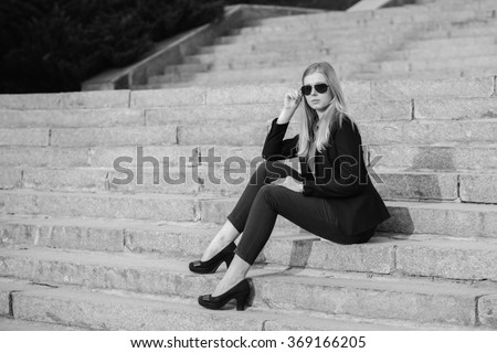 Beautiful pretty girl in sunglasses sitting on the stairs. Girl stylish dressed walking around the city.