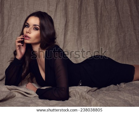 Beautiful pretty girl lying on textile background in black sexy mini dress. Fashion or glamour style portrait of young stylish sensual woman with long dark curly hair. - stock photo