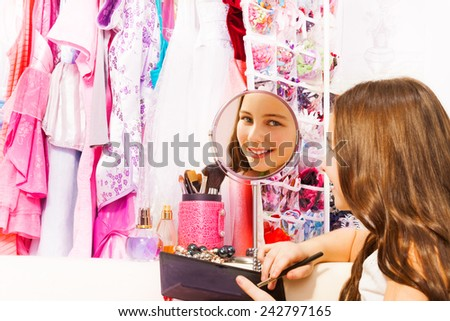 Beautiful pretty girl smiles in round mirror