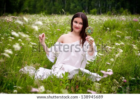 Beautiful pretty happy smiling girl (young woman) sitting on green summer meadow and  looking in the mirror.  Love to yourself, natural self-love concept. - stock photo