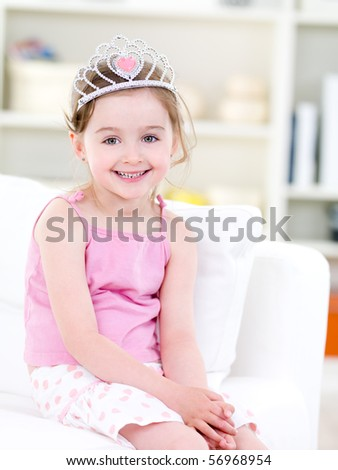 Beautiful pretty little girl with happy smile sitting on the sofa with crown - indoors - stock photo