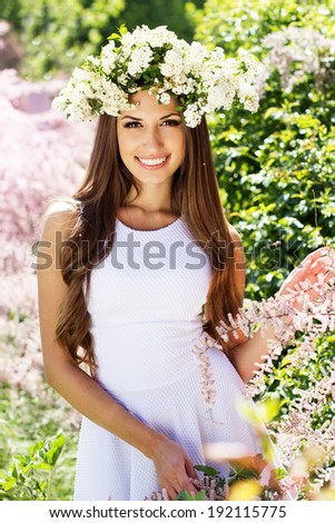 Beautiful pretty  smiling girl on the nature in wreath of white flowers - stock photo