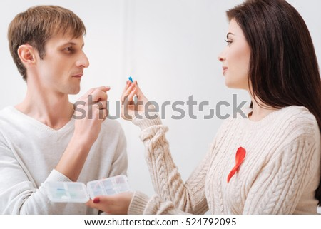Beautiful pretty woman giving a pill to her boyfriend