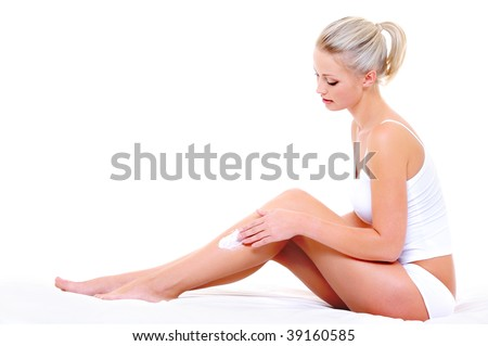 Beautiful pretty woman sitting on bed  applying moisturizer cream on her slim legs