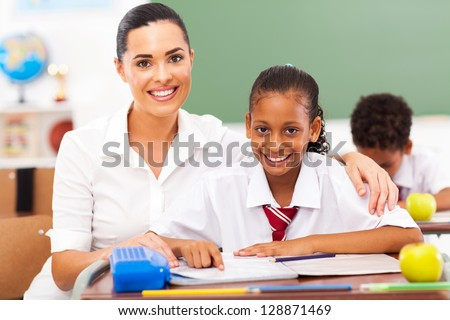 beautiful primary school teacher and students in classroom - stock photo