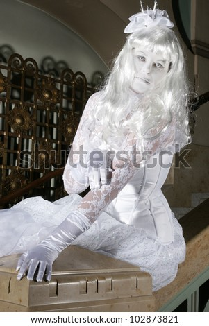 Beautiful princess all in white with a little crown sitting on a balustrade - stock photo