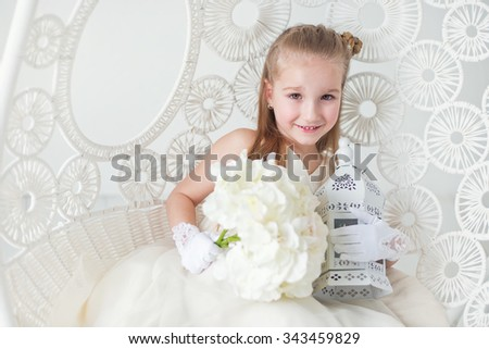 Beautiful princess girl sit on lace swing with white flowers in elegant dress posing ready to celebrate wedding and birthday party - stock photo