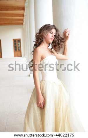 beautiful princess in golden dress near pillars - stock photo