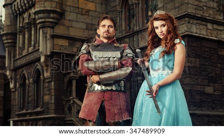 Beautiful princess is giving sword to her brave knight. Ancient castle on the background. - stock photo