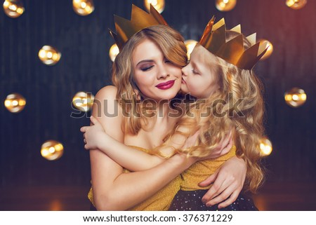 Beautiful princess mother and daughter in a gold crown - stock photo