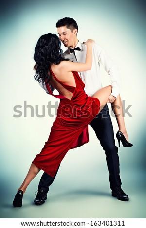 Beautiful professional artists dancing passionate dance. Studio shot. - stock photo