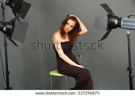 beautiful professional female model resting between shots in photography studio shoot set-up - stock photo