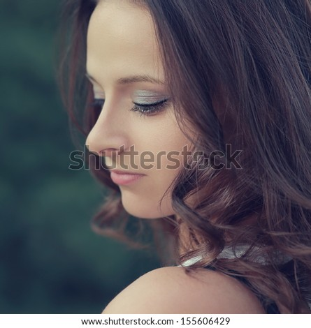 Beautiful profile of romantic girl face looking down outdoors. Closeup portrait