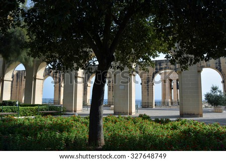 Beautiful public garden with arches, columns and trees. - stock photo