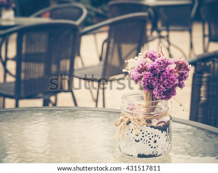 Beautiful purple flowers bunch on table glass in summer season. : Photo in vintage style. - stock photo