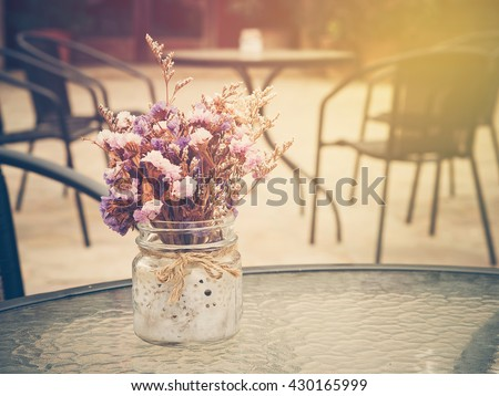 Beautiful purple flowers bunch on table glass with sunlight and summer season. : Photo in vintage style. - stock photo