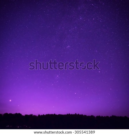 Beautiful purple night sky with many stars above the forest. Milkway space background - stock photo