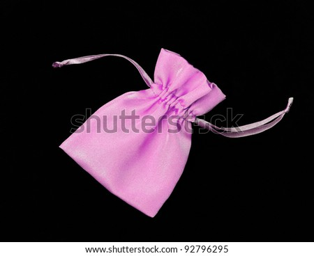 Beautiful Purple / Pink Silk Pouch to hold Jewelry and Delicate items isolated on Black Velvet Background - stock photo