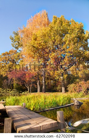Beautiful quiet park in bright autumnal colors with small footbridge - stock photo