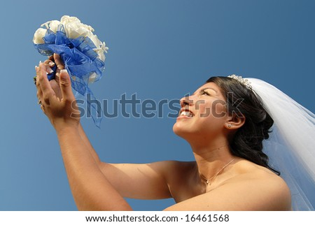 Beautiful, radiant bride holding her bouquet of flowers - stock photo