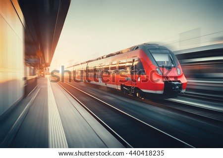 Beautiful railway station with modern high speed red commuter train with motion blur effect at colorful sunset in Nuremberg, Germany. Railroad with vintage toning - stock photo