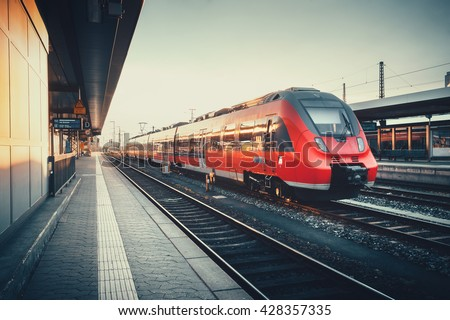 Beautiful railway station with modern red commuter train at colorful sunset in Nuremberg   , Germany. Railroad with vintage toning - stock photo