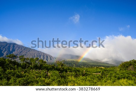 Beautiful rainbow as seen from East Maui's south coast on Piilani Highway. The mountains belong to Haleakala crater, which summits at 10,027 ft. Beautiful sunny day with some clouds - Maui, Hawaii. - stock photo