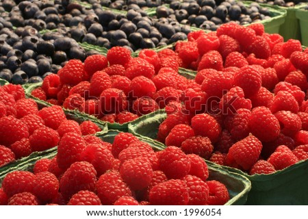 Beautiful raspberries and blueberries at the market. - stock photo