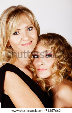 beautiful real couple mother in her 40s and teenage daughter wearing evening wear and make-up in studio - stock photo