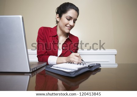 Beautiful receptionist writing notes in book - stock photo
