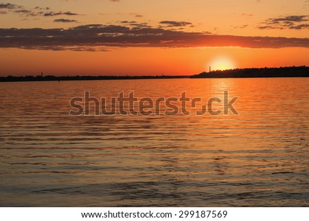 Beautiful red and orange sunset over the river with the sun and clouds reflected in the water