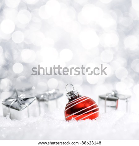 Beautiful red and silver Christmas decoration with snow in the background - stock photo
