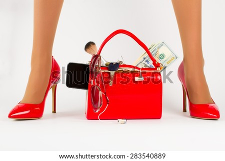 Beautiful red bag with accessories stands between red shoes.