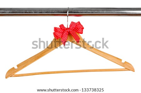 Beautiful red bow hanging on wooden hanger isolated on white - stock photo