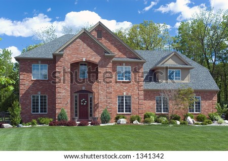 Beautiful red brick  home. Very colorful photo with blue sky and green grass. Typical new home in the suburbs of the United States. Just one of many home or house photos in my gallery. - stock photo