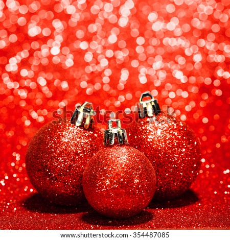 Beautiful red christmas balls on abstract glitter background close-up - stock photo