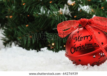 """Beautiful red Christmas bell ornament lies in the snow with copyspace and a message of """"Merry Christmas."""" - stock photo"""
