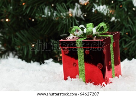 Beautiful red Christmas gift lies in the snow with a Christmas tree background. Shallow DOF. - stock photo