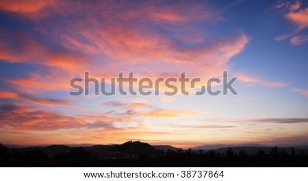 Beautiful red clouds in blue sky with silhouette of Campobasso castle - stock photo