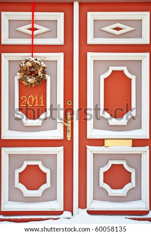 Beautiful red door decorated with Christmas wreath with numerals of New year - stock photo