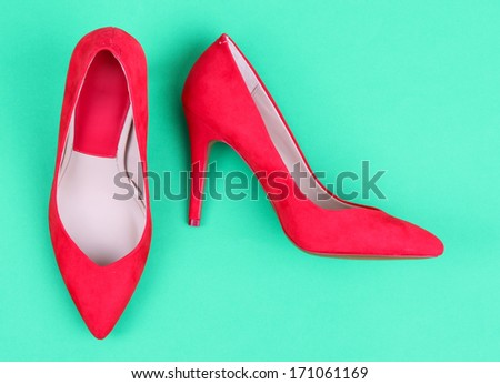 Beautiful red female shoes, on green background