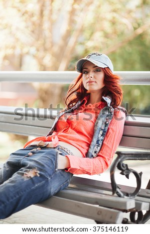 Beautiful red hair girl in casual on the bench