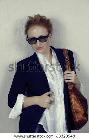 beautiful red hair woman in fashion black jacket and white shirt wearing brown leather bag and trendy sunglasses - double shadow is part of the effect. - stock photo