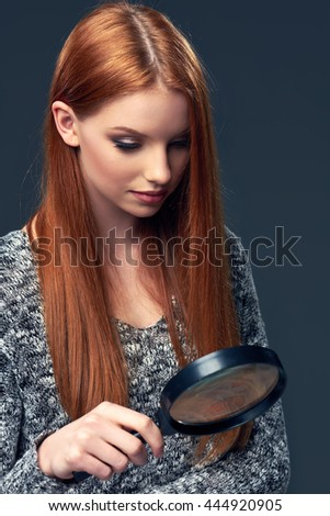 Beautiful red hair woman looking through magnifying glass - stock photo