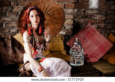 beautiful red hair woman with japanese parasol sitting on sofa - stock photo