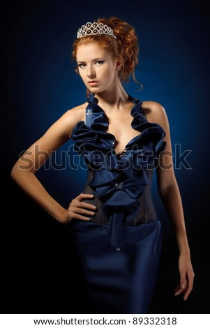 Beautiful red-haired fashion model posing in evening dress over dark blue background - stock photo