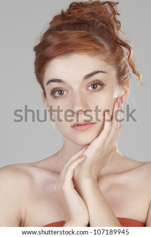 Beautiful  red haired girl at age of nineteen putting her hands near her face and looking at the camera close up