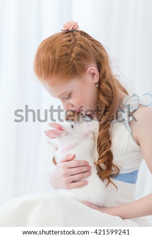 Beautiful red-haired girl child presented a rabbit in a gift box. - stock photo