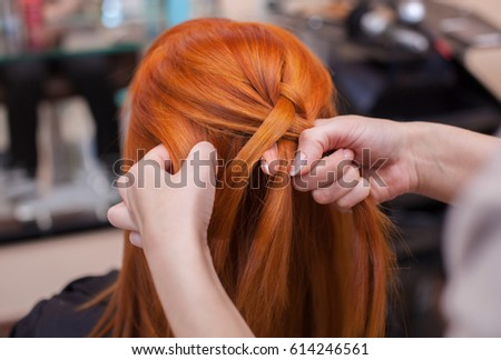 Beautiful red-haired girl, hairdresser weave a French braid close-up, in a beauty salon. Professional hair care and creating hairstyles.