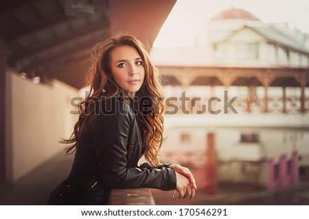 Beautiful red-haired girl in a leather jacket in the urban landscape / Young fashionable woman - stock photo